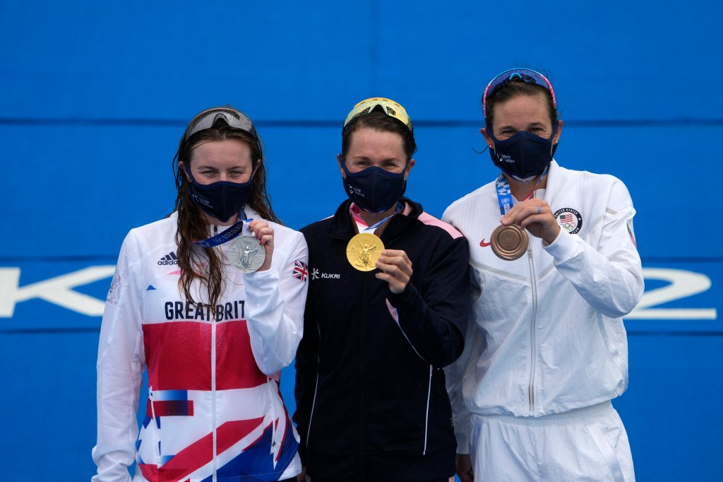 Gold medal winner Flora Duffy of Bermuda, center, hugs silver medalist Georgia Taylor-Brown of Great Britain, left, and Katie Zaferes of The United States during a medal ceremony for the women's individual triathlon competition at the 2020 Summer Olympics on July 27, 2021, in Tokyo, Japan.