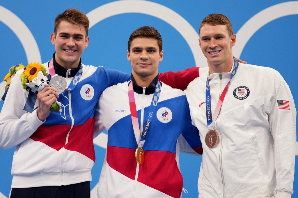 Gold medalist Evgeny Rylov, centre, of the Russian Olympic Committee stands with compatriot and silver medalist Kliment Kolesnikov, left, and bronze medalist Ryan Murphy of the United States after the men's 100-meter backstroke final at the 2020 Olympics on July 27, 2021, in Tokyo, Japan.