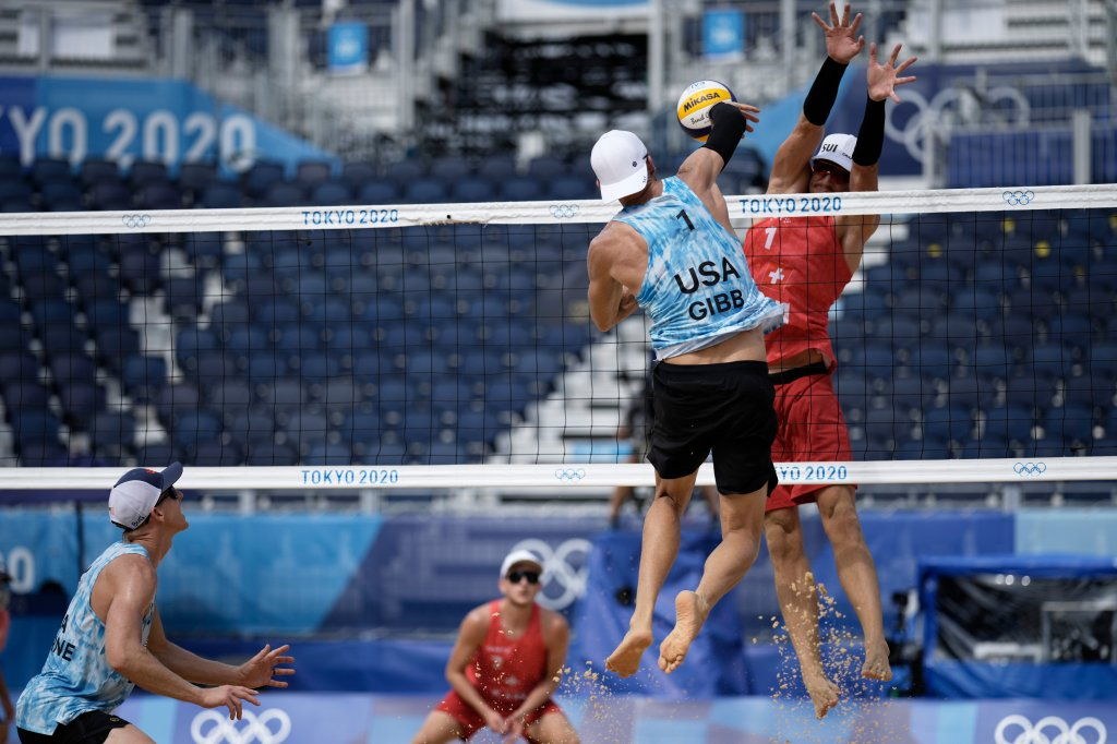 Jacob Gibb, top left, of the United States, takes a shot as Adrian Heidrich, of Switzerland, defends during a men's beach volleyball match at the 2020 Summer Olympics, Wednesday, July 28, 2021, in Tokyo, Japan.