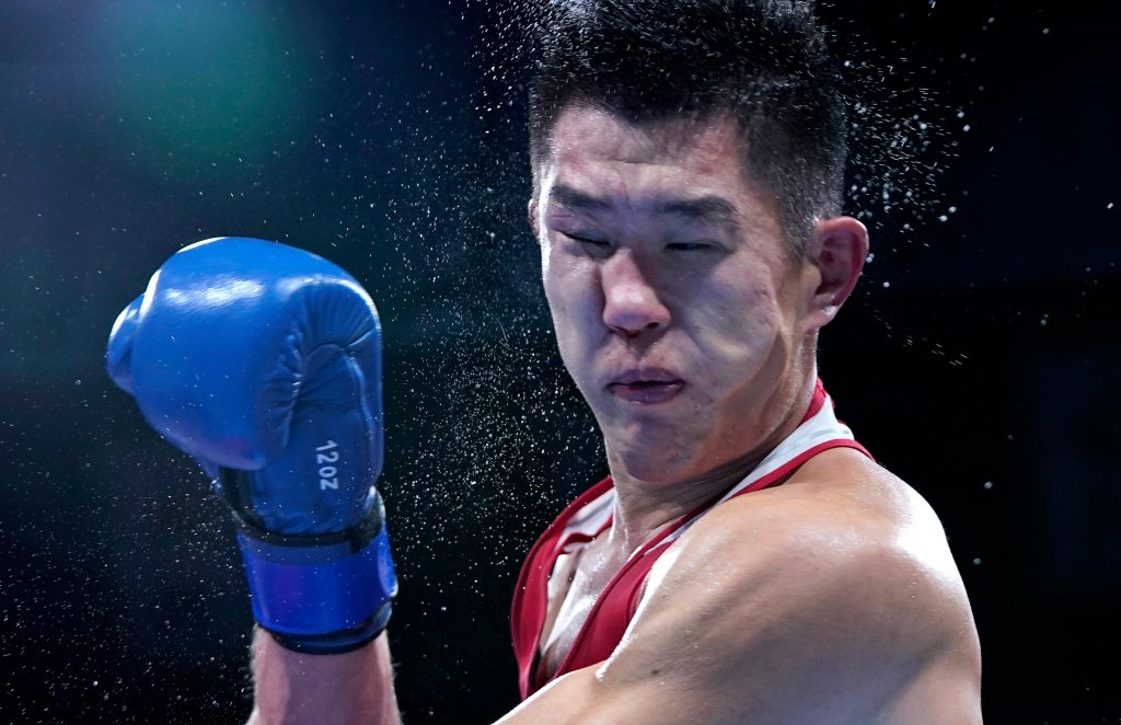 Russian Olympic Committee's Imam Khataev delivers a punch to Kazakhstan's Bekzad Nurdauletov during the men's light heavyweight 81-kg preliminaries boxing match at the 2020 Summer Olympics, Wednesday, July 28, 2021, in Tokyo, Japan.