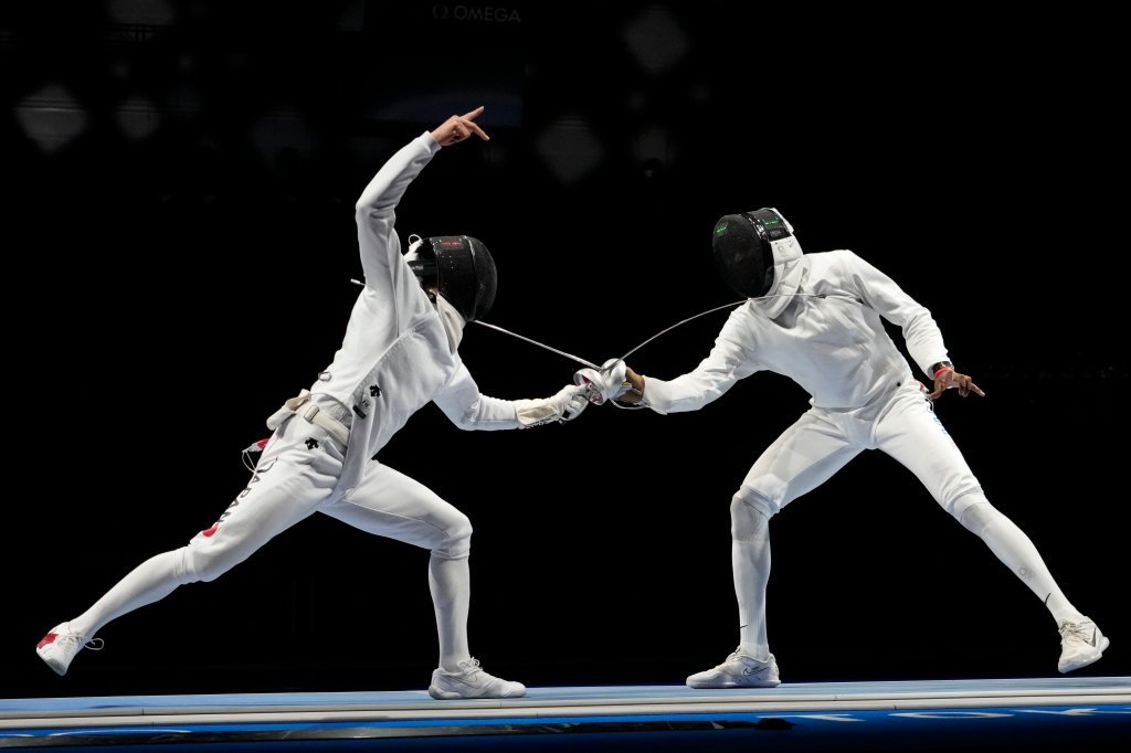 Kazuyasu Minobe of Japan, left, and Yeisser Ramirez of the United States compete in the men's Epee team round of 16