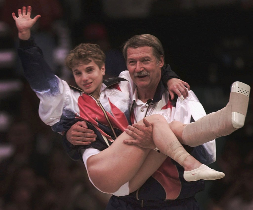 USA's Kerri Strug is carried by her coach, Bela Karolyi, as she waves to the crowd on her way to receiving her gold medal for the women's team gymnastics competition, at the Centennial Summer Olympic Games in Atlanta on Tuesday, July 23, 1996. Strug suffered two torn ligaments and a sprained ankle from the vault competition.