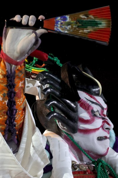A Kabuki actor holds a fan above his head