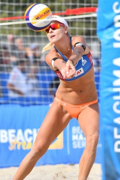 A beach volleyball player serves.