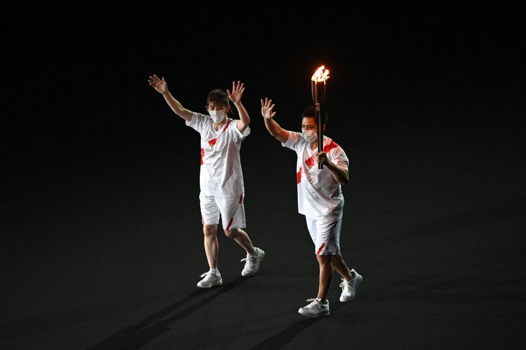 Torchbearers carry the Olympic torch as they enter the Olympic Stadium during the opening ceremony of the Tokyo 2020 Olympic Games, in Tokyo, on July 23, 2021.