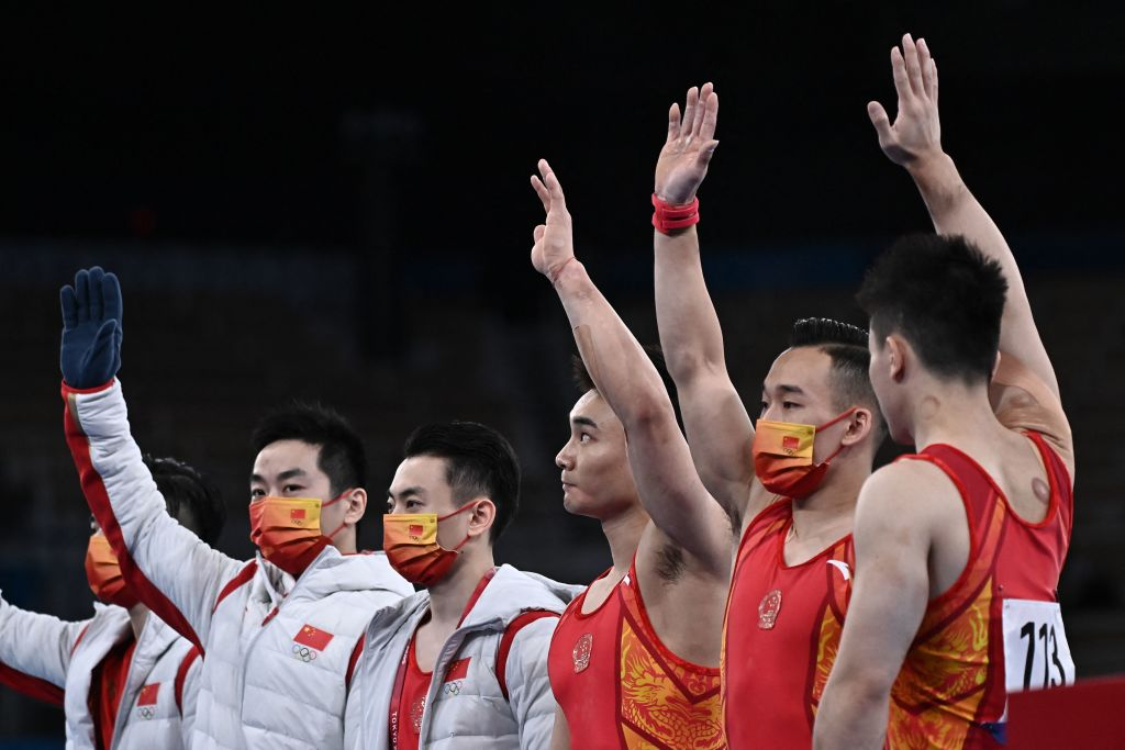Chinesische Teammitglieder winken vor der Gymnastik-Qualifikation der Herren