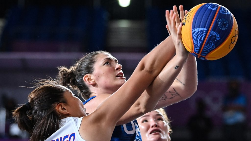 Mongolia's Solongo Bayasgalan, left, fights for the ball with USA's Stefanie Dolson, center, during the women's first round 3x3 basketball match at the Aomi Urban Sports Park in Tokyo, on July 24, 2021.