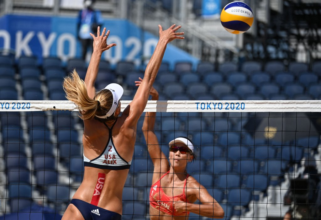 USA's Alix Klineman (L) blocks a shot by China's Xue Chen in their women's preliminary beach volleyball pool B match between the USA and China during the Tokyo 2020 Olympic Games at Shiokaze Park in Tokyo on July 25, 2021.