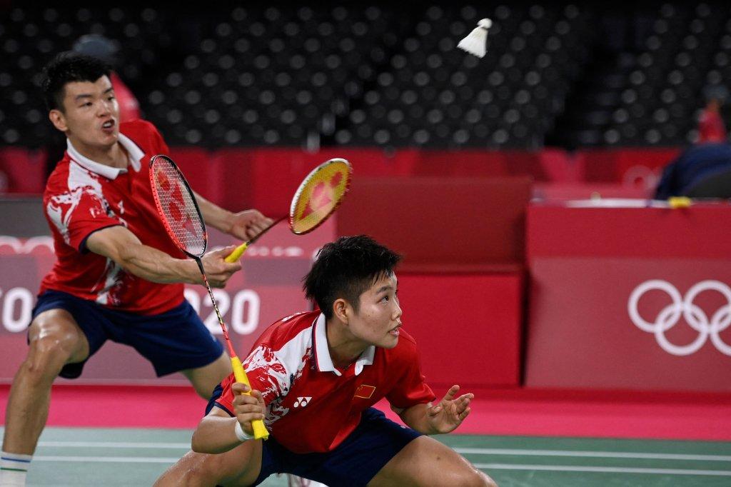 China's Wang Yilyu (L) hits a shot next to China's Huang Dongping in their mixed doubles badminton