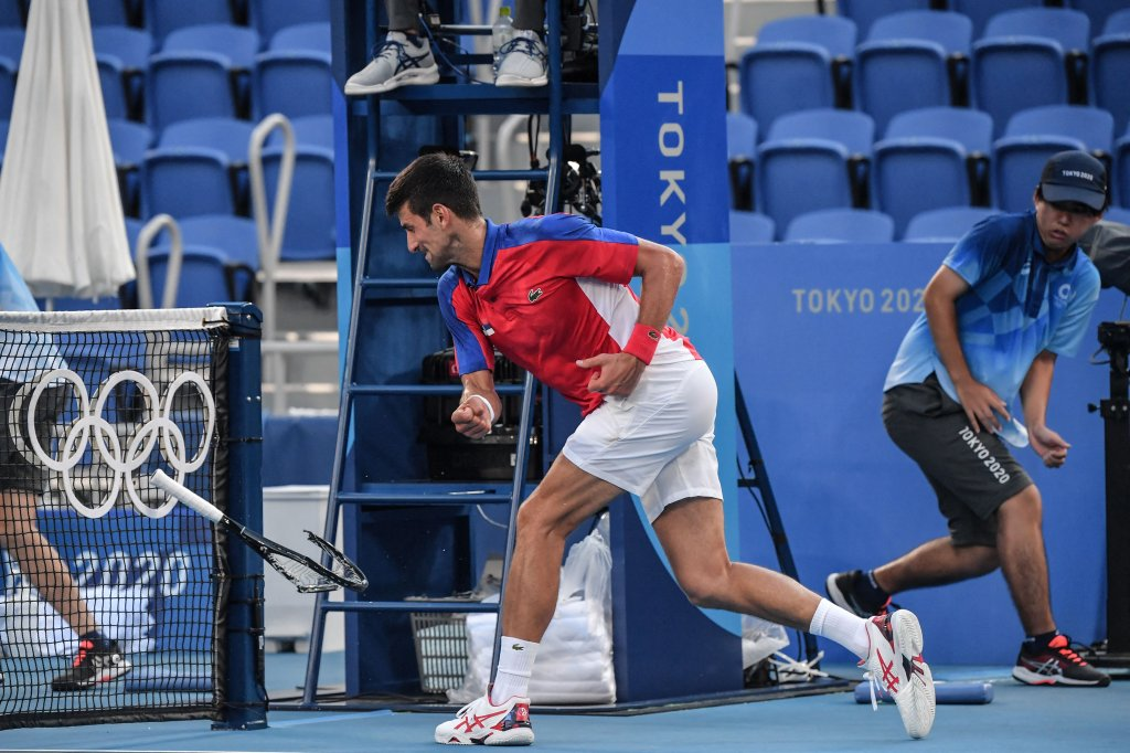 Serbia's Novak Djokovic smashes his racket during his Tokyo 2020 Olympic Games men's singles tennis match for the bronze medal against Spain's Pablo Carreno Busta at the Ariake Tennis Park in Tokyo on July 31, 2021.