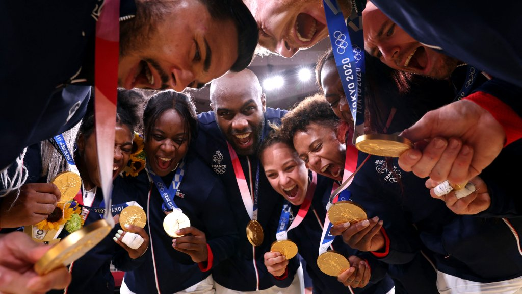 Team France celebrates with the gold medal during the podium ceremony for the judo mixed team of the Tokyo 2020 Olympic Games at the Nippon Budokan in Tokyo on July 31, 2021.