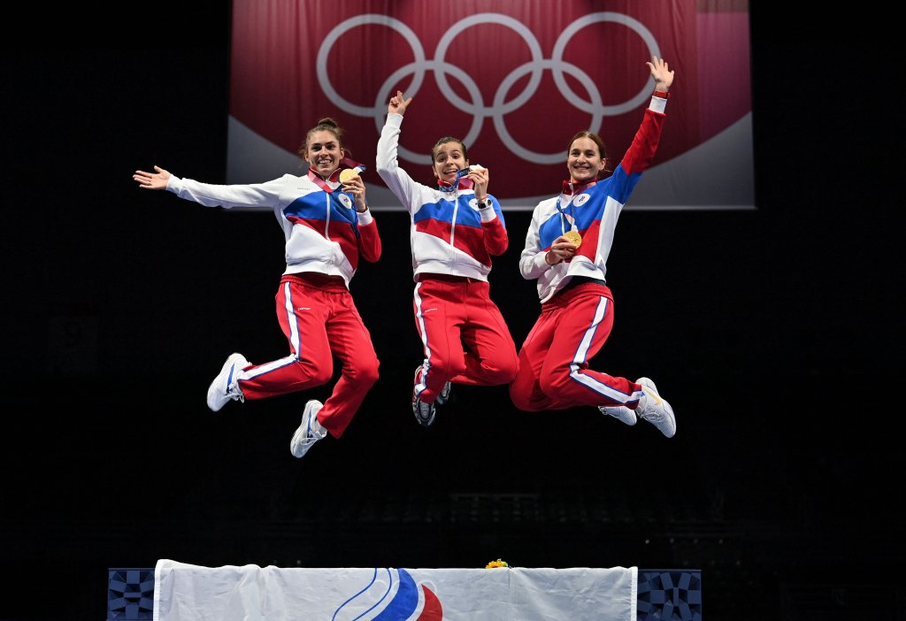 Gold medallist Russia's sabre team celebrate on podium during the medal ceremony for the womens team sabre during the Tokyo 2020 Olympic Games at the Makuhari Messe Hall in Chiba City, Chiba Prefecture, Japan, on July 31, 2021.