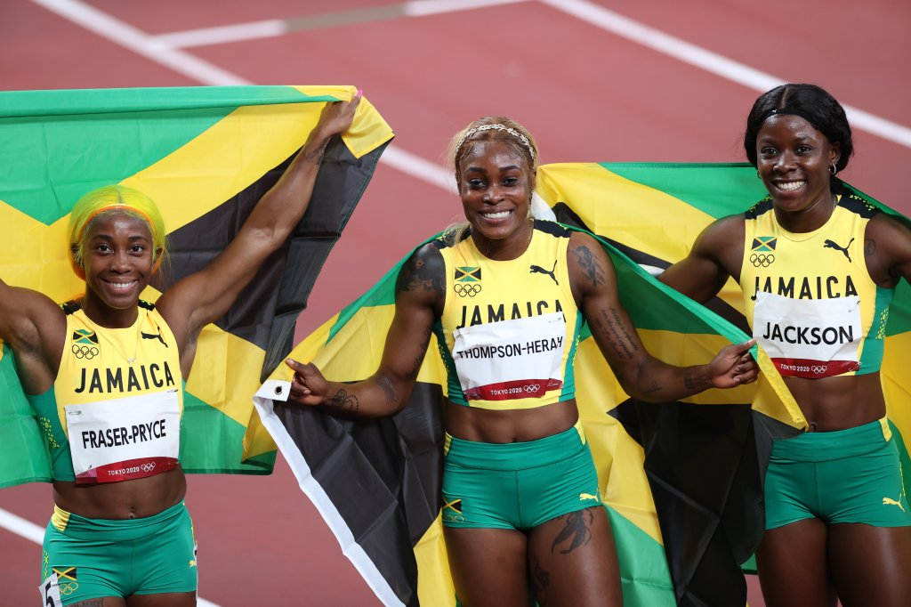 From left: Jamaica's runner-up Shelly-Ann Fraser-Pryce, first-place finisher Elaine Thompson Herah and third-place finisher Shericka Jam Jackson celebrate with flags after the women's 100-meter, July 31, 2021, Tokyo, Japan.