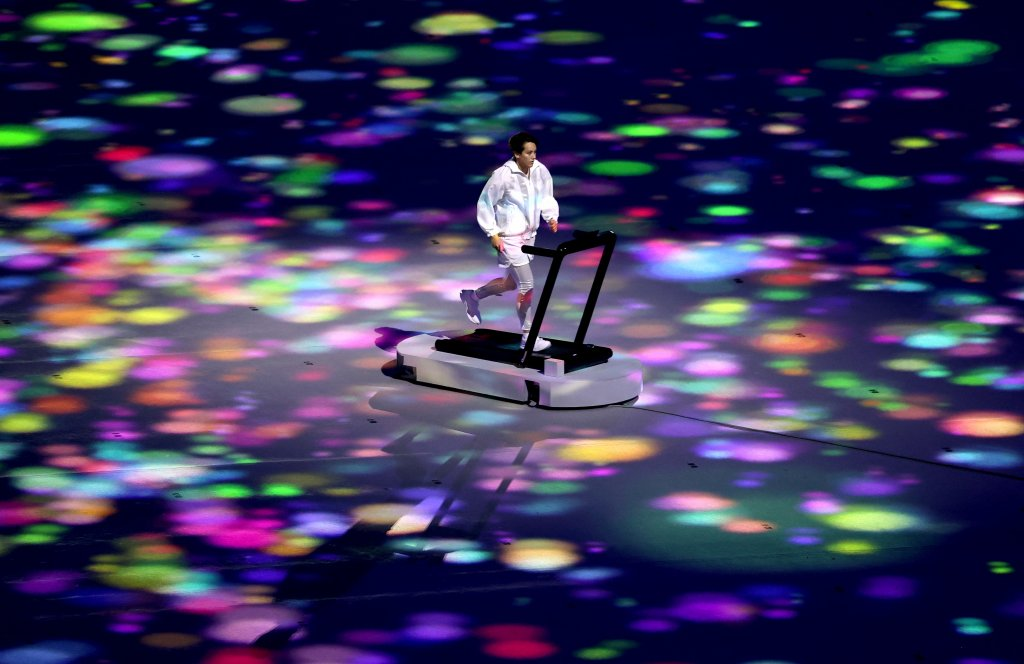 A performer symbolizing athletes training alone, yet still united with all, runs on a treadmill during the Opening Ceremony of the Tokyo 2020 Olympic Games at Olympic Stadium on July 23, 2021 in Tokyo, Japan.