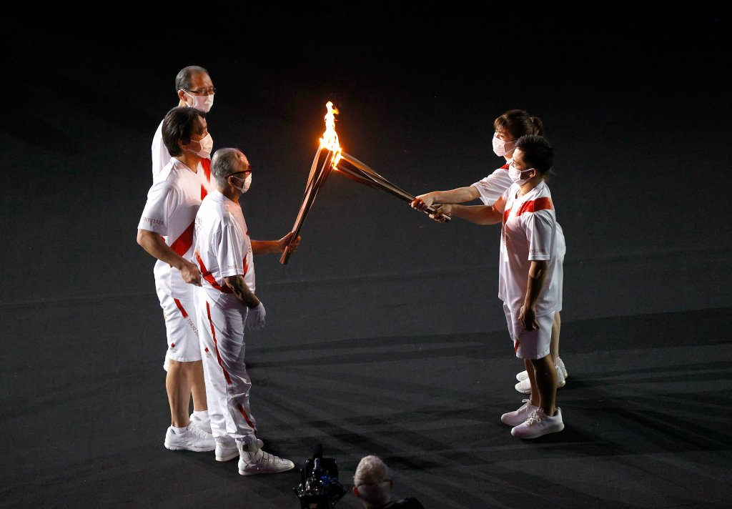 Torch carriers exchange the flame of the Olympic torch during the Opening Ceremony of the Tokyo 2020 Olympic Games at Olympic Stadium on July 23, 2021 in Tokyo, Japan.