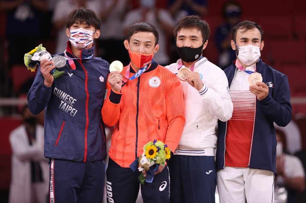 Silver medallist Wei Yung Yang of Chinese Taipei, gold medallist Naohisa Takato of Team Japan, bronze medallist A, Yeldos Smetov of Kazakhstan and bronze medallist B, Luka Mkheidze of Team France pose on the podium for the Men's Judo 60kg Final on day one of the Tokyo 2020 Olympic Games at Nippon Budokan on July 24, 2021, Tokyo, Japan.