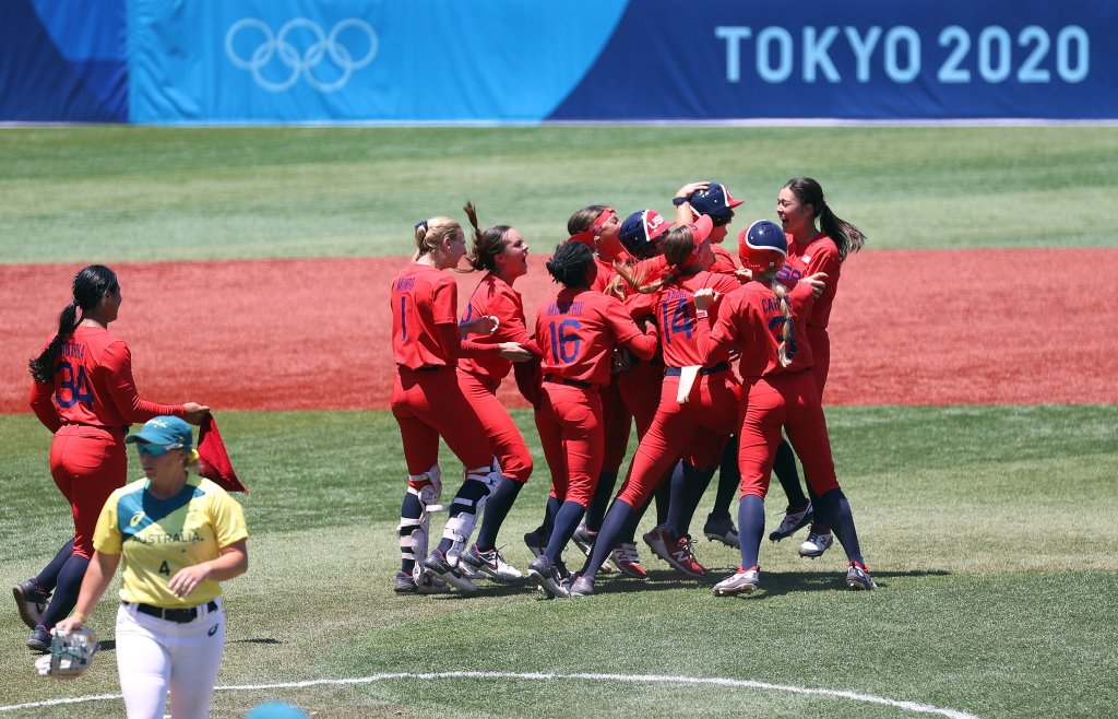 Team United States players mob teammate Amanda Chidester #4 after she hit a two-run RBI single in the eighth inning to win the game 2-1 as Stacey Mcmanus #4 of Team Australia looks on after their game during the Softball Opening Round on day two of the Tokyo 2020 Olympic Games at Yokohama Baseball Stadium on July 25, 2021, in Yokohama, Kanagawa, Japan.
