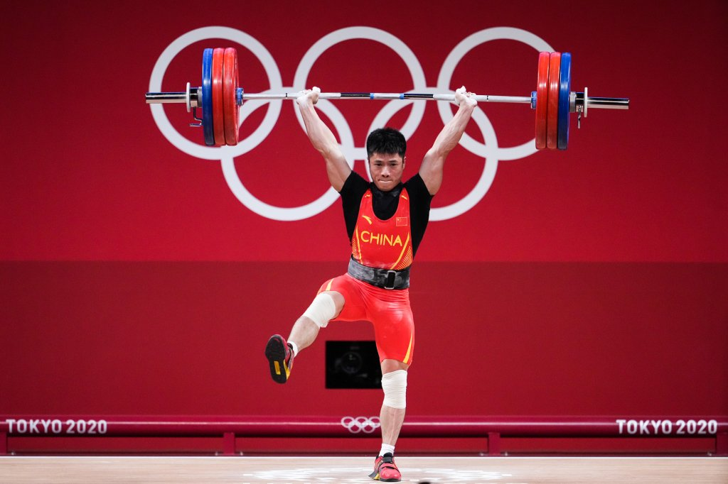 Li Fabin of Team China competes in the Men's 61kg Weightlifting Group A match on day two the Tokyo 2020 Olympic Games at the Tokyo International Forum on July 25, 2021 in Tokyo, Japan. Li set an Olympic record, lifting 313kg for the event.
