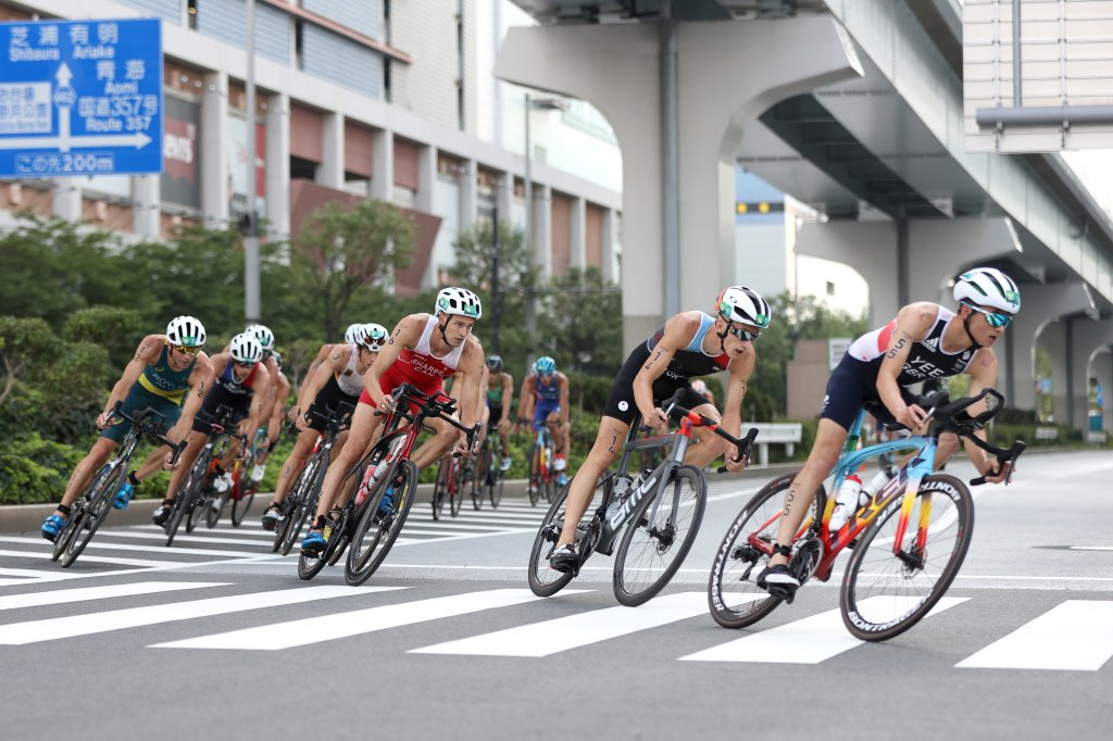 Alex Yee of Team Great Britain rides ahead of Stefan Zachaus of Team Luxembourg, Matthew Sharpe of Team Canada and other competitors during the Men's Individual Triathlon on day three of the Tokyo 2020 Olympic Games at Odaiba Marine Park on July 26, 2021 in Tokyo, Japan.