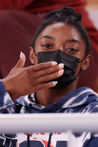 Simone Biles, wearing a mask, blows a kiss