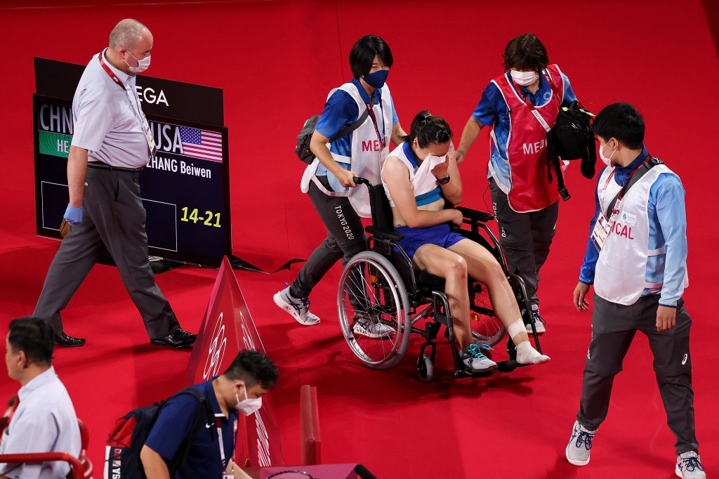Beiwen Zhang (in wheelchair) of Team United States reacts after suffered a match-ending injury