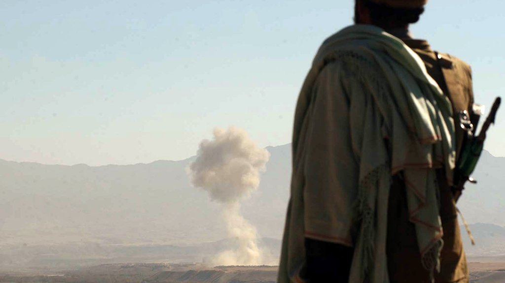 A Northern alliance Mujahed looks on as a U.S. aircraft release its load of bombs, Nov. 7, 2001.