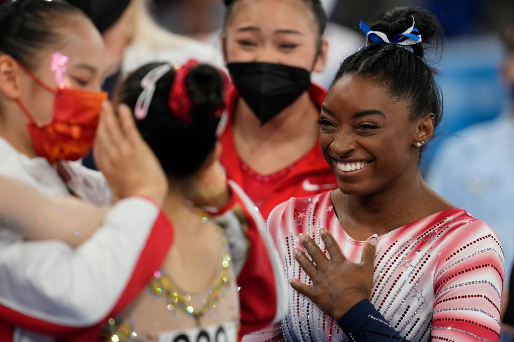 Simone Biles, of the United States, smiles as Tang Xijing, of China, left, embraces teammate Guan Chenchen after the latter won the gold medal