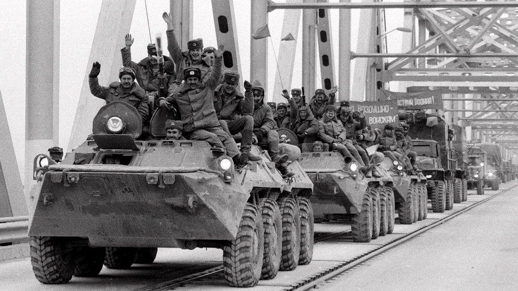 Soviet Army soldiers wave their hands as their last detachment crosses a bridge on the border between Afghanistan and then Soviet Uzbekistan near the Uzbek town of Termez, Feb. 15, 1989.