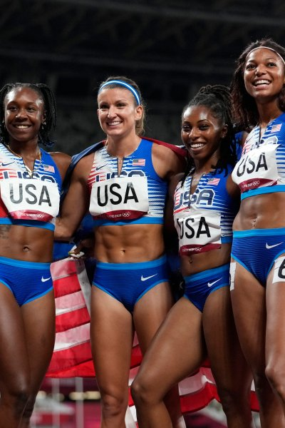 The U.S. women's 4x100m relay team poses with the American flag