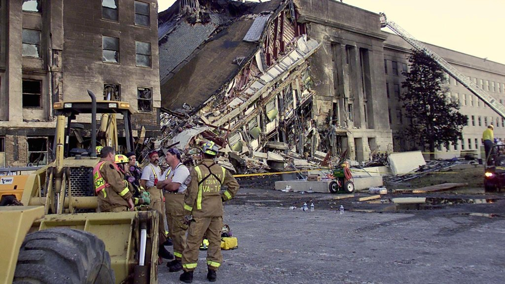 Firefighters take a break at the site of the terrorist attack at the Pentagon, Sept. 11, 2001. The terrorists struck the World Trade Center Towers in New York City and the Pentagon.