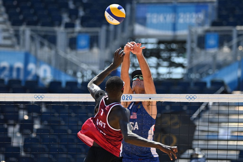 Qatar's Cherif Younousse (L) attempts a shot past USA's Philip Dalhausser in their men's beach volleyball round of 16 match between Qatar and the USA during the Tokyo 2020 Olympic Games at Shiokaze Park in Tokyo on August 1, 2021.