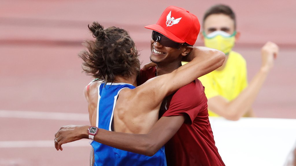 Mutaz Essa Barshim of Qatar and Gianmarco Tamberi of Italy hug, Aug. 1, 2021. The two have decided to share first place golds in high jump.