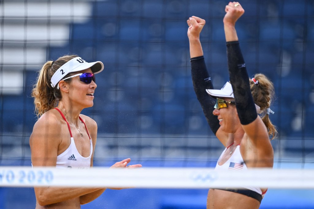 USA's Alix Klineman (L) celebrates winning with partner April Ross after their women's beach volleyball quarter-final match between Germany and the USA during the Tokyo 2020 Olympic Games at Shiokaze Park in Tokyo on Aug. 3, 2021.
