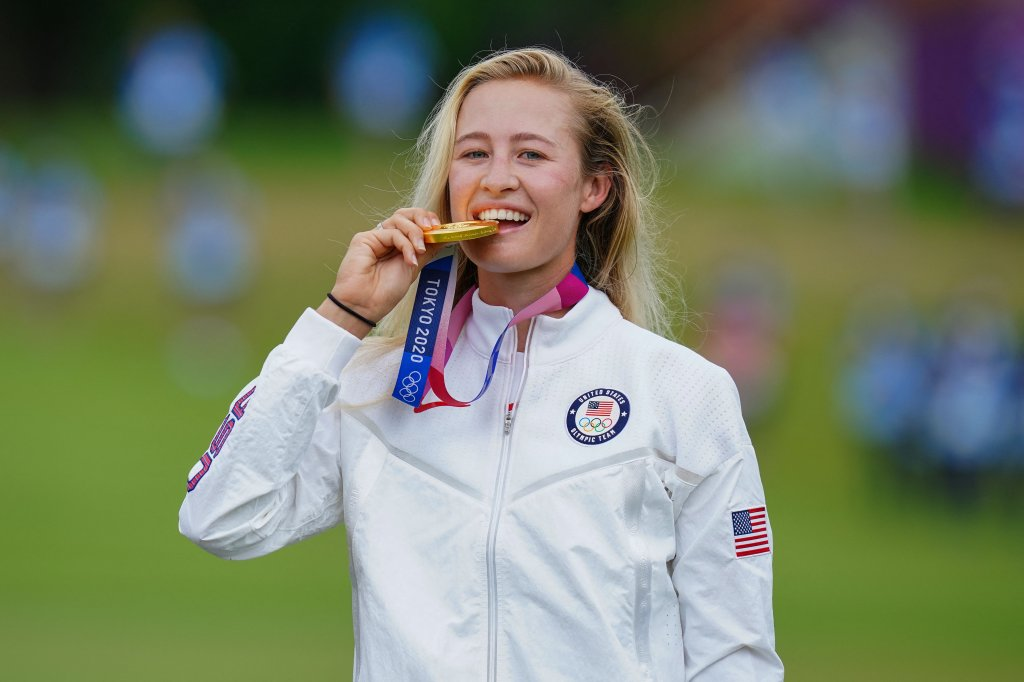 Gold medallist Nelly Korda of Team USA bites her medal on the podium during the victory ceremony of the women's golf individual stroke play during the Tokyo 2020 Olympic Games at the Kasumigaseki Country Club in Kawagoe on Aug. 7, 2021.