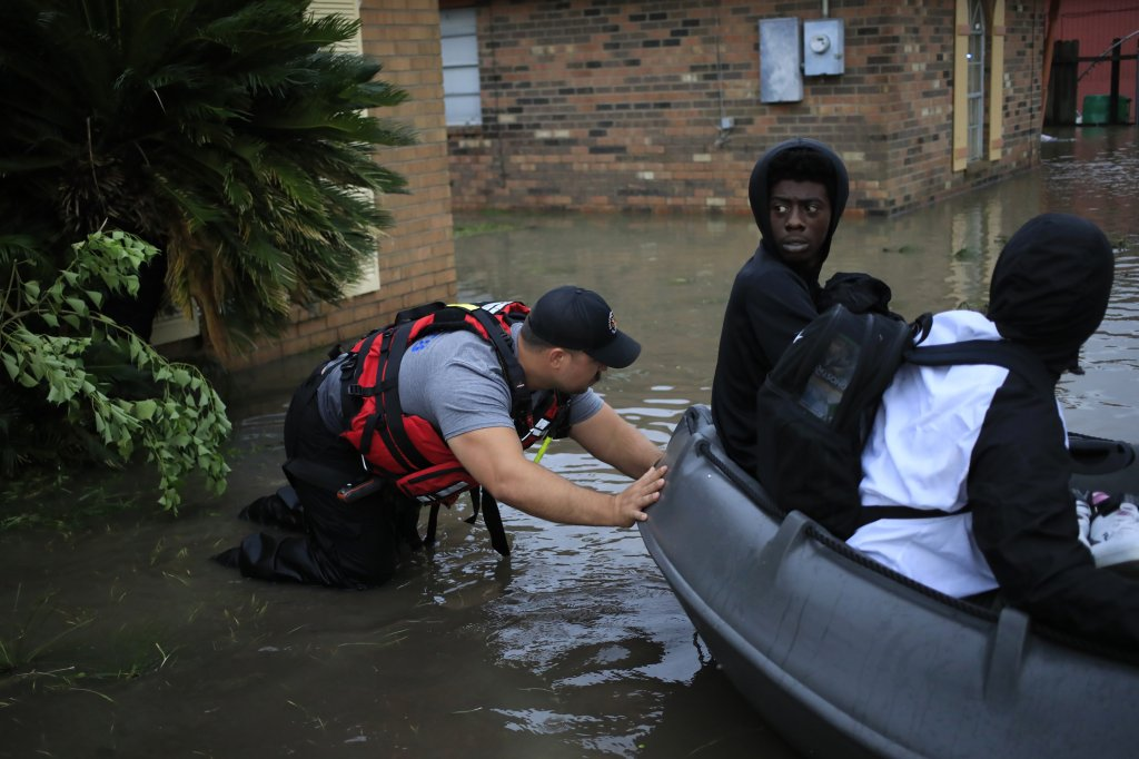 A first responder pushes a rescue boat with residents aboard through floodwaters left behind by Hurricane Ida in LaPlace, Louisiana, U.S., on Monday, Aug. 30, 2021.