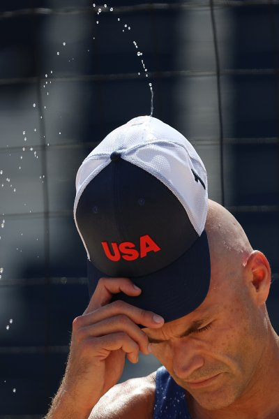 Sweat flies from the hat of Philip Dalhausser #1 of Team United States between plays against Team Qatar during the Men's Round of 16 beach volleyball on day nine of the Tokyo 2020 Olympic Games at Shiokaze Park on August 1, 2021 in Tokyo, Japan.