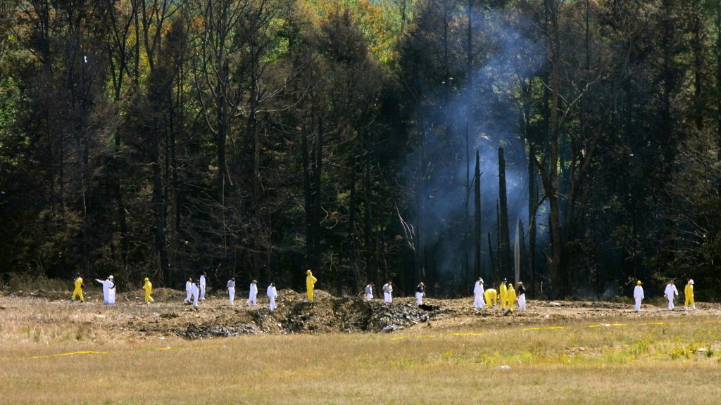 Emergency workers look over the site where the Boeing 757 of United Airlines crashed near Shanksville, Pennsylvania.