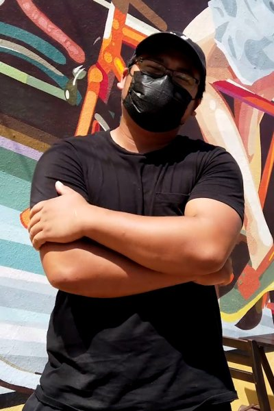 Masked man stands with arms folded in front of mural of bicycle.