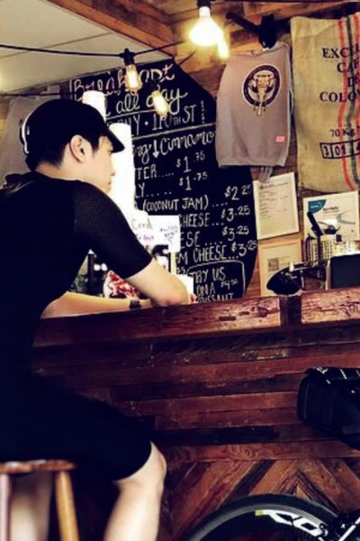 Two Asian men sit at cafe counter with bicycle against counter.