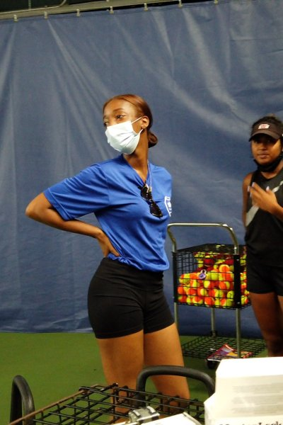 Girl wearing mask holds hand on her hip on an indoor tennis court.