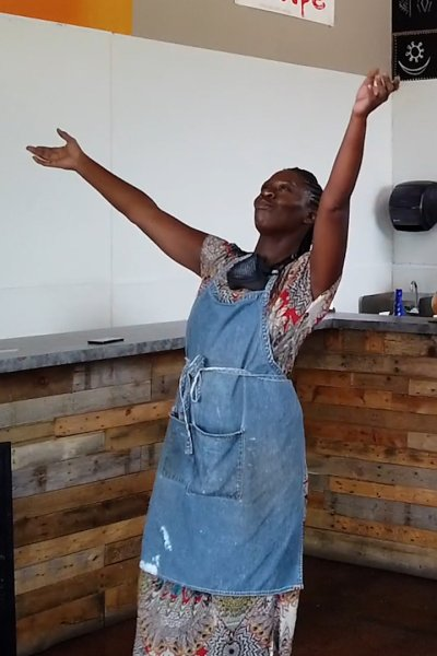 A woman dances in her cafe