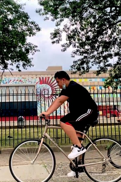 Men wearing masks ride bikes on Philadelphia sidewalk.