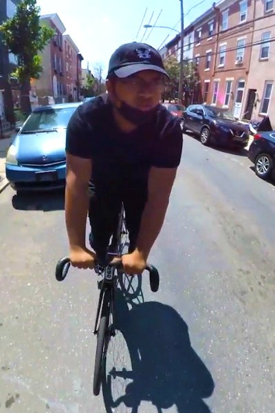Man rides bicycle through streets of Philadelphia with mask pulled down to chin.